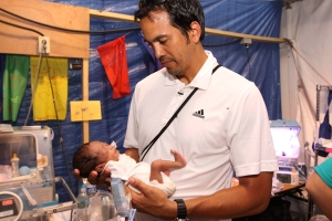 Miami Heat Head Coach Erik Spoelstra with baby at field hospital in Haiti